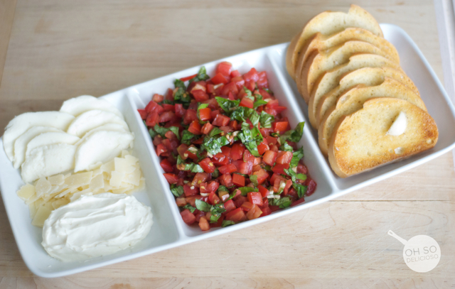 A plate filled with tomatoes, mozzarella and bread for making an easy bruschetta bar
