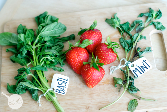 fresh basil strawberries and mint herb on wooden cutting board