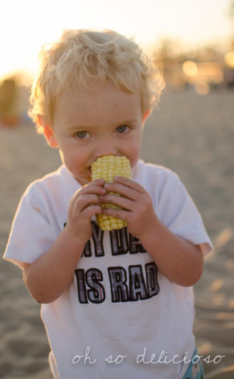 A small boy eating saltwater corn on the cob