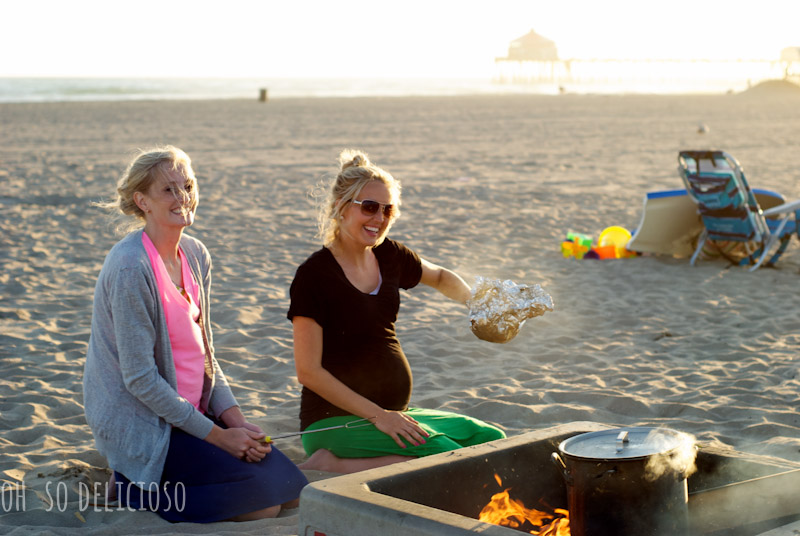 Two women sitting on the beach making saltwater corn on the cob